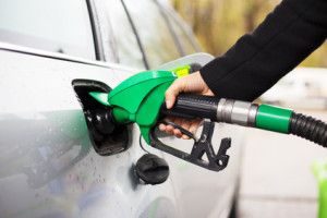 Hand holding fuel pump and refilling car at petrol station